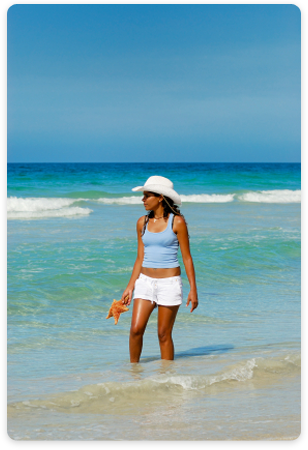 Woman on the beach in Los Roques holding a starfish.